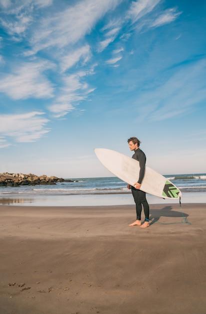 Jeune Surfeur Debout Dans L'océan Avec Sa Planche De Surf Dans Un Costume De Surf Noir. Concept De Sport Et De Sports Nautiques. Photo gratuit