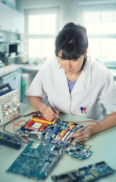 Un jeune technicien ou ingénieur répare du matériel électronique dans un centre de recherche Photo Premium