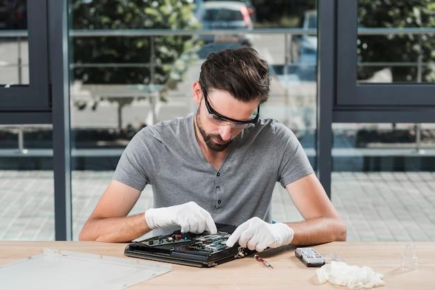 Jeune technicien en réparation d'ordinateur en atelier Photo gratuit