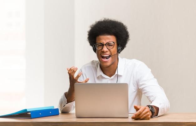 Jeune télémarketeur homme noir très effrayé et effrayé Photo Premium