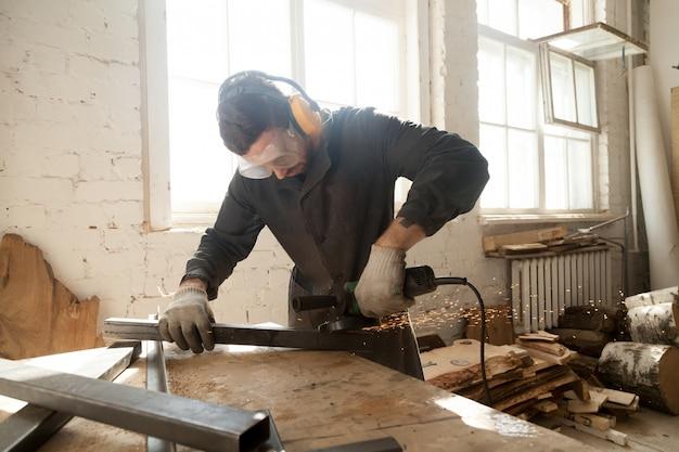 Jeune travailleur meulant acier profilé en métal en atelier intérieur Photo gratuit