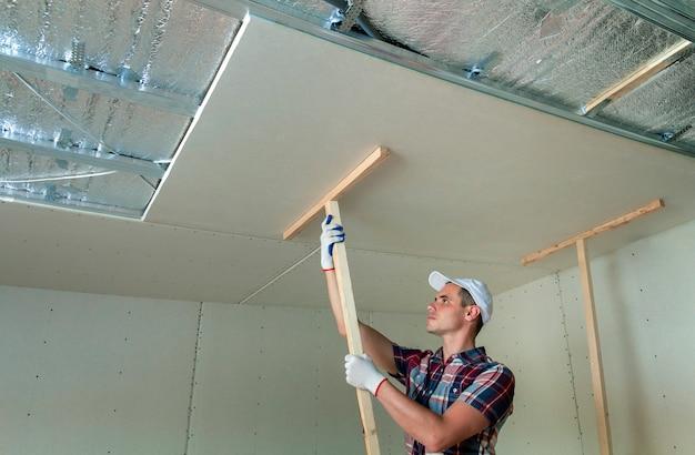 Jeune travailleur portant des gants de protection fixant des supports en bois pour plafond suspendu en placoplâtre au cadre métallique. Photo Premium