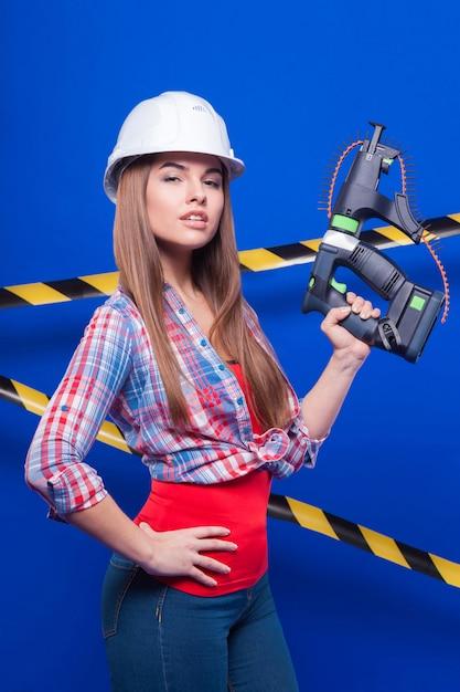 Jeune travailleuse sexy en chemise à carreaux, casque blanc et jeans, debout, avec pistolet Photo Premium