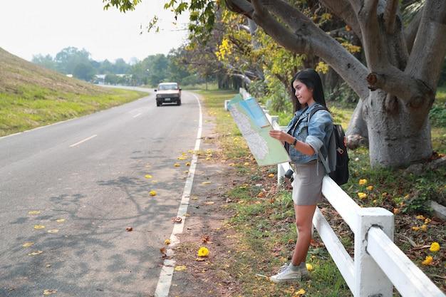 Jeune voyageur asiatique cherchant la direction sur la carte de localisation lors de voyages pendant les vacances Photo Premium