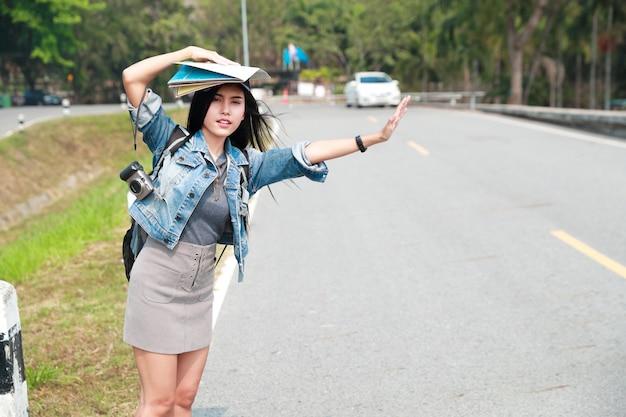 Jeune voyageur asiatique avec sac à dos, attendant la voiture sur la route en voyageant pendant les vacances Photo Premium