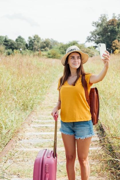 Jeune voyageur avec bagages prenant un selfie Photo gratuit