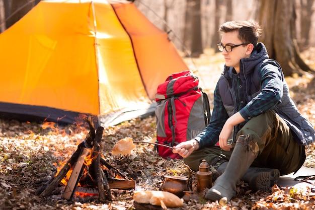Un jeune voyageur dans la forêt se repose près de la tente et prépare un petit-déjeuner dans la nature Photo Premium