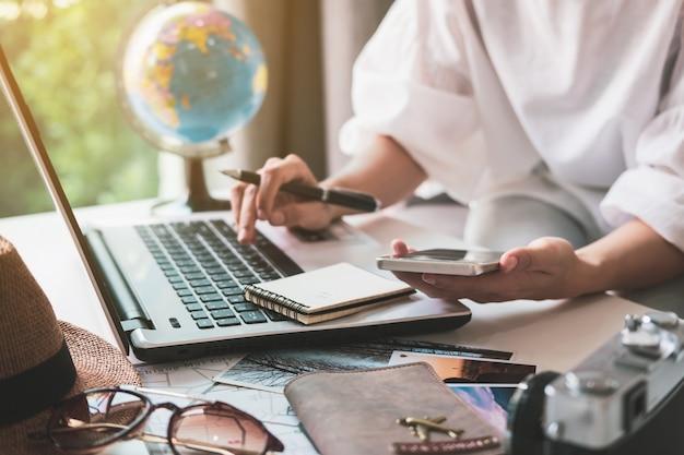 Jeune voyageur préparant son voyage de vacances et cherchant des informations ou réservant un hôtel sur ordinateur portable Photo Premium