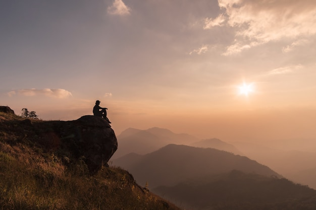 Jeune voyageur se détendre et regarder beau paysage au sommet de la montagne, concept de mode de vie aventure voyage Photo Premium