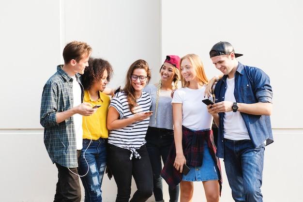 Jeunes adultes amis à l'aide de smartphones ensemble à l'extérieur du concept de culture de la jeunesse Photo Premium