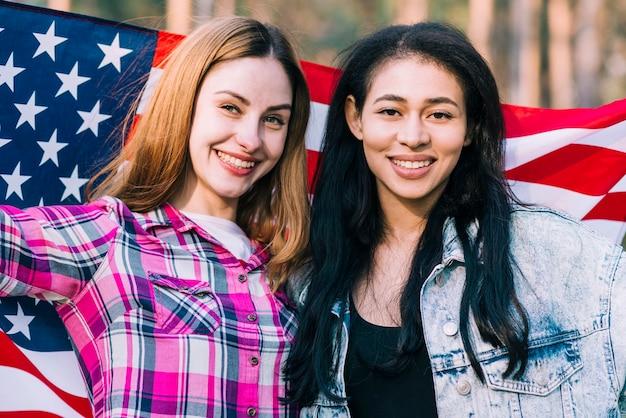 Jeunes amies agitant un drapeau américain le jour de l'indépendance Photo gratuit
