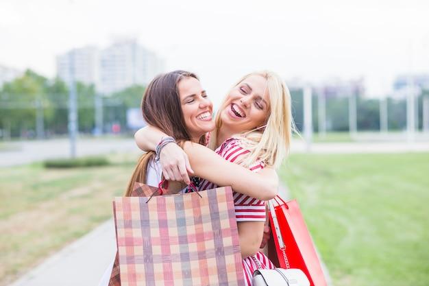 Jeunes amies s'embrassant en tenant des sacs à provisions Photo gratuit
