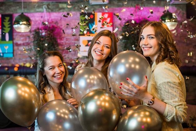 Jeunes amies tenant des ballons d'argent profitant en fête Photo gratuit