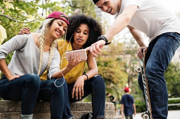 Jeunes amis adultes utilisant un smartphone et écoutant de la musique en plein air Photo Premium