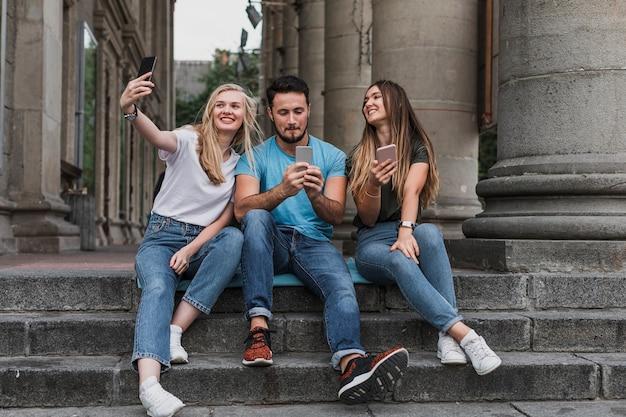 Jeunes Amis Assis Dans Les Escaliers Et Prenant Un Selfie Photo gratuit