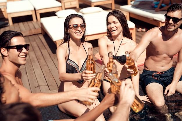 Jeunes amis avec des boissons alcoolisées au bord de la piscine Photo Premium