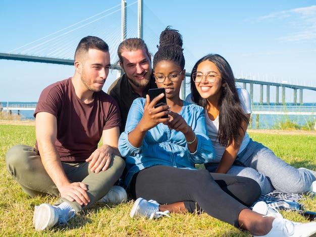 Jeunes amis ciblés utilisant un smartphone en plein air Photo gratuit