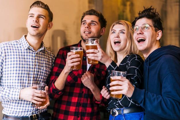 Jeunes amis enthousiastes appréciant la bière en regardant quelque chose Photo gratuit