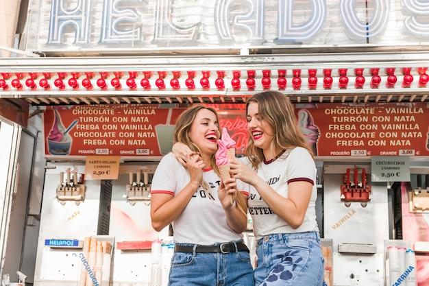Jeunes amis, manger des glaces dans le parc d'attractions Photo gratuit