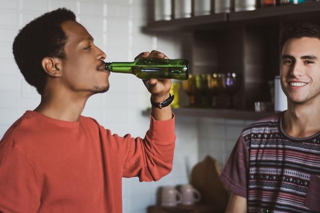 Jeunes amis s'amusant avec des bouteilles à la maison. Photo Premium