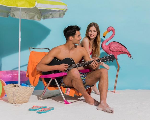 Jeunes amoureux se détendre sur la plage en studio Photo gratuit