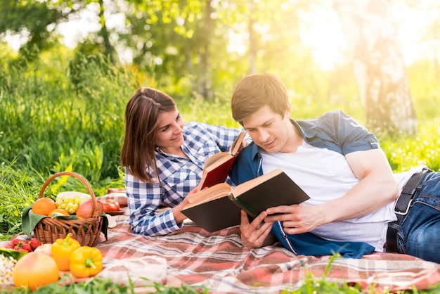 Jeunes amoureux se reposant sur un plaid et lisant des livres Photo gratuit