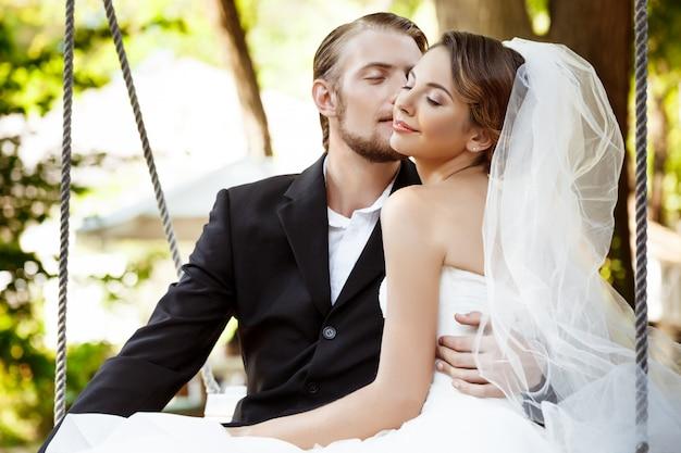 Jeunes Beaux Jeunes Mariés Souriant, Embrassant, Assis Sur Une Balançoire Dans Le Parc. Photo gratuit