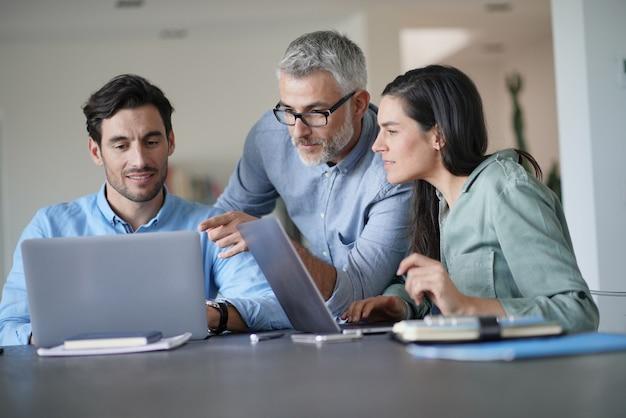 Jeunes collègues avec un ancien patron travaillant avec des ordinateurs Photo Premium