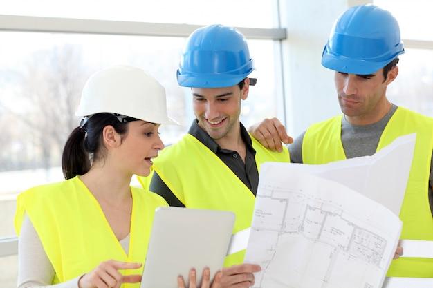 Jeunes collègues ouvriers du bâtiment regardant le plan de construction Photo Premium