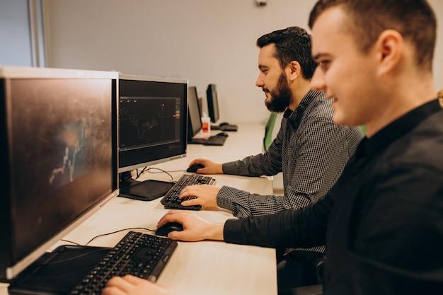 Jeunes Concepteurs De Sites Web Masculins Travaillant Sur Un Ordinateur Photo gratuit
