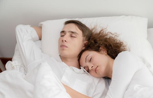 Jeunes couples amoureux dormant ensemble au lit à la maison Photo Premium