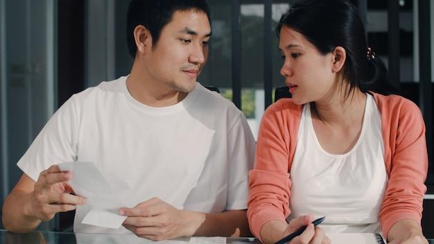 Jeunes couples de femmes enceintes asiatiques enregistrent leurs revenus et leurs dépenses à la maison. maman et papa heureux d'utiliser un budget record pour ordinateur portable, les taxes, un document financier, le commerce électronique dans le salon à la maison. Photo gratuit