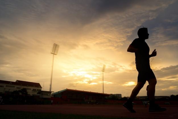 Les jeunes courent au stade sur un magnifique coucher de soleil. Photo Premium