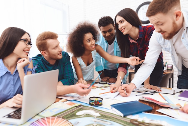 De jeunes designers de différentes races discutent des couleurs pour le design Photo Premium
