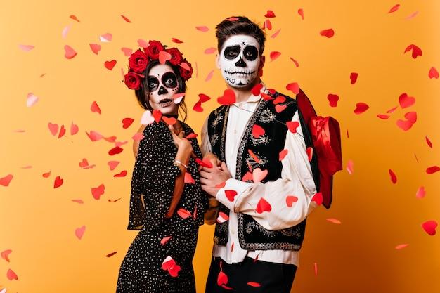Jeunes Drôles Dansant à La Fête Latine à Halloween. Couple En Vêtements De Mascarade Posant Sur Le Mur Jaune. Photo gratuit