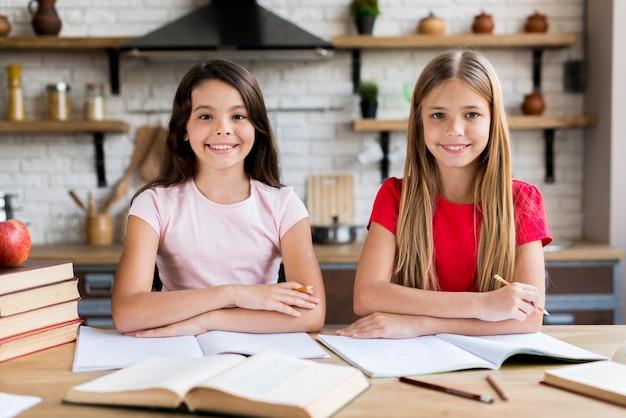 Jeunes écolières souriantes assis au bureau et faisant de l'exercice à la maison Photo gratuit