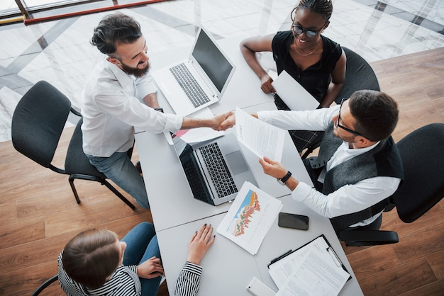 Jeunes Employés Assis Au Bureau à La Table Et à L'aide D'un Ordinateur Portable, Un Concept De Réunion De Remue-méninges De Travail D'équipe. Photo gratuit