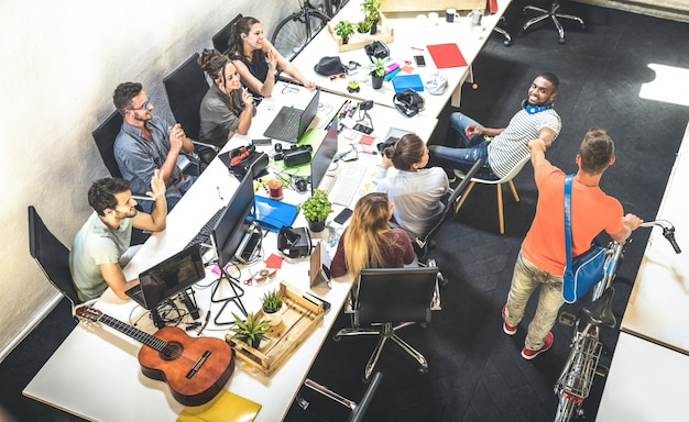 Jeunes employés ouvriers s'amusant au démarrage de studio alternatif urbain Photo Premium