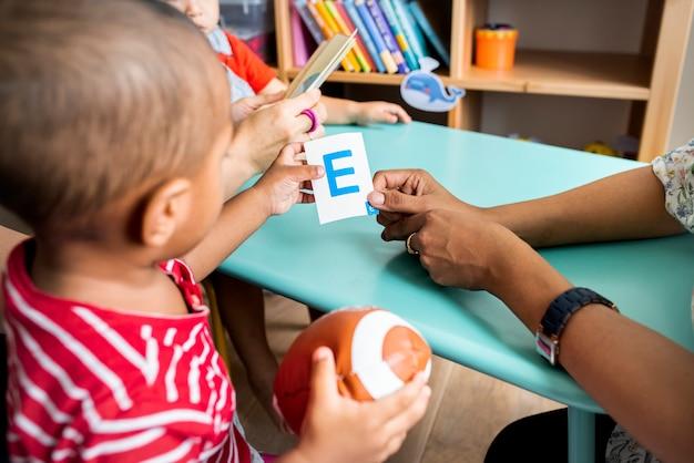 Jeunes enfants apprenant l'alphabet anglais avec leurs parents Photo Premium