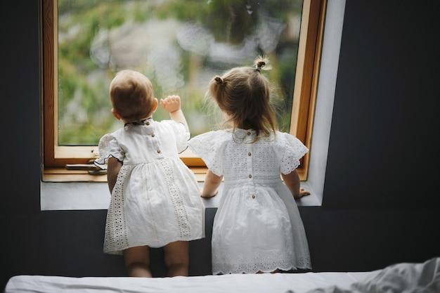 Les jeunes enfants regardent curieusement par la fenêtre Photo gratuit