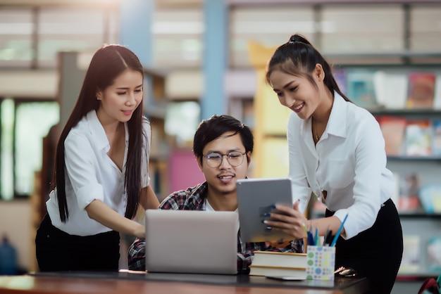 Jeunes étudiants en apprentissage, étagères de bibliothèque Photo gratuit