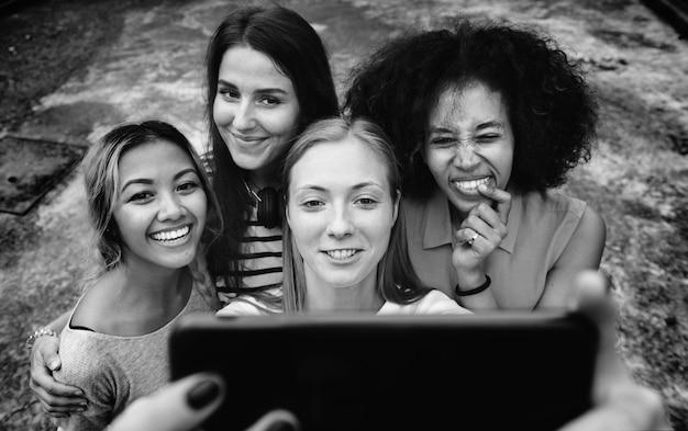 Jeunes femmes adultes amis prenant un groupe selfie Photo gratuit