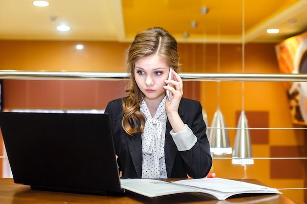 Jeunes femmes d'affaires assis dans un café avec un ordinateur portable et parlant au téléphone mobile Photo Premium