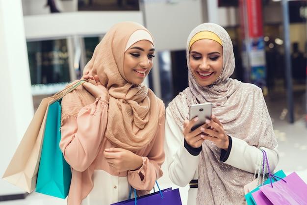 Jeunes femmes arabes utilisant un smartphone avec un ami Photo Premium