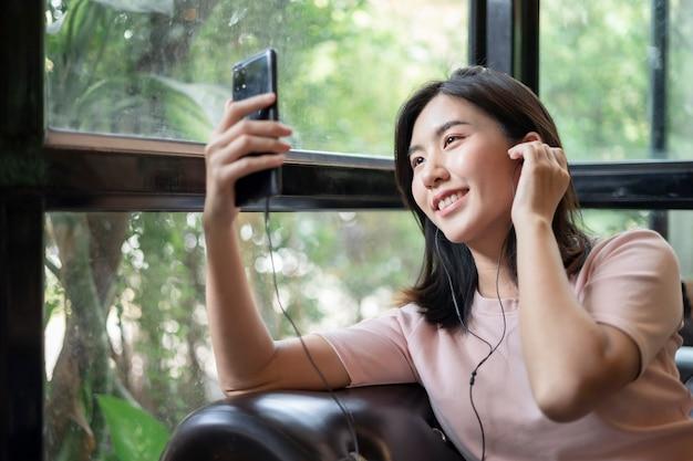 Les Jeunes Femmes Asiatiques Gèrent Des Emplois Via Les Téléphones Portables. Femme Asiatique Portant Des écouteurs Et écoutant De La Musique Sur Son Téléphone Mobile. Photo Premium