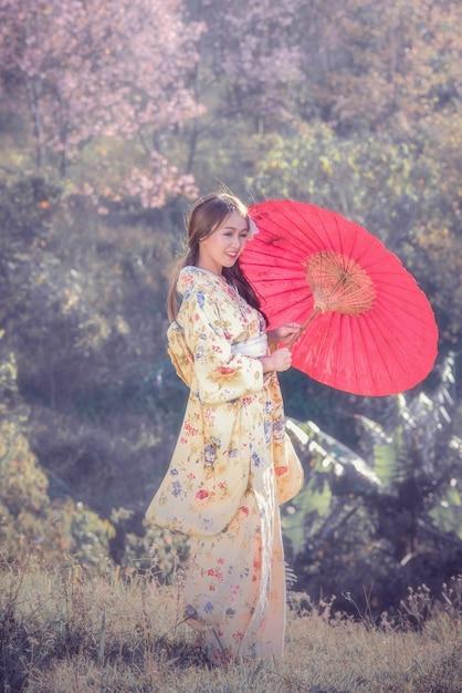 Jeunes femmes asiatiques portant un kimono japonais traditionnel avec un parapluie rouge dans le parc de fleurs de cerisier. Photo Premium