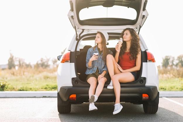 Jeunes femmes assises sur le coffre de la voiture Photo gratuit