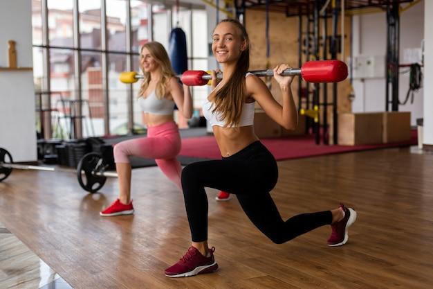 Jeunes femmes au gymnase soulever des poids Photo gratuit