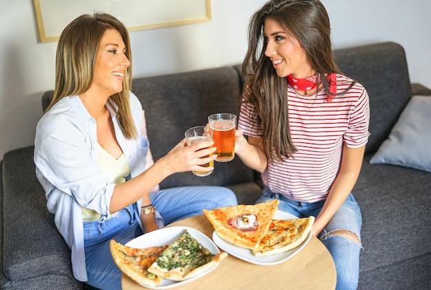 Jeunes Femmes, Avoir Déjeuner, Ensemble, Griller Bières, Et, Manger Pizza Photo Premium