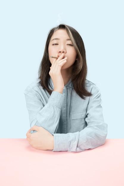 Jeunes Femmes Coréennes Fumant Un Cigare Assis à Table Au Studio. Couleurs Tendance Photo gratuit